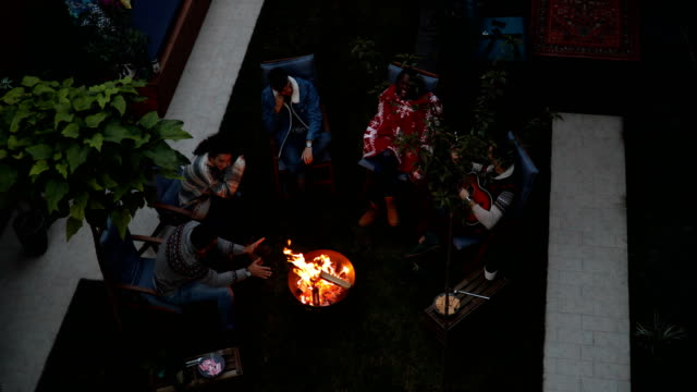 top view of a group of friends gathered around a fire pit - marshmallow video stock e b–roll