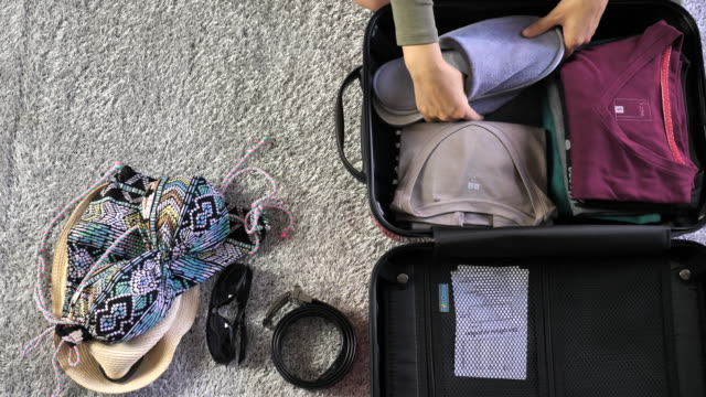 top view of a young woman packing clothes into luggage at hotel, slow motion - packing stock videos and b-roll footage