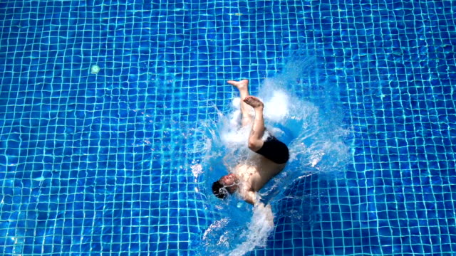 slo mo - top view of asian man trying to do backflip into swimming pool - fallimento video stock e b–roll