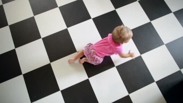 Top view of baby girl crawling on tiled floor