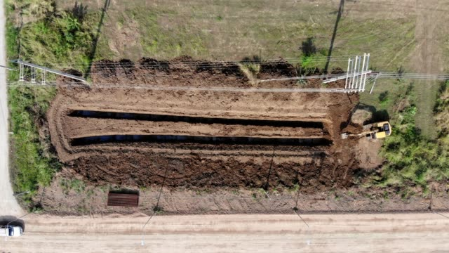 top view of backhoe loader digging soil furrow in plantation - bulldozer stock videos & royalty-free footage