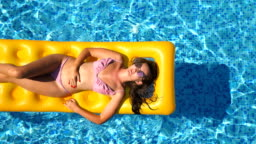 Top view of beautiful tanned girl in sunglasses and pink bikini lying on yellow inflatable mattress in swimming pool. Young woman relaxing in basin of hotel during summer travel. Concept of vacation. Close up