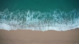 Top view of blue waves crashing against sand beach