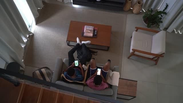 自宅でスマートフォンでゲームをしているリビングルームの兄弟のトップビュー - マッチ点の映像素材/bロール