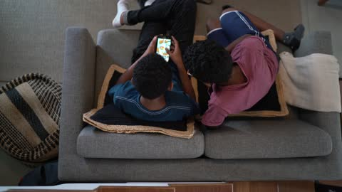 top view of brothers in the living room playing games on smartphone at home - brother stock videos & royalty-free footage