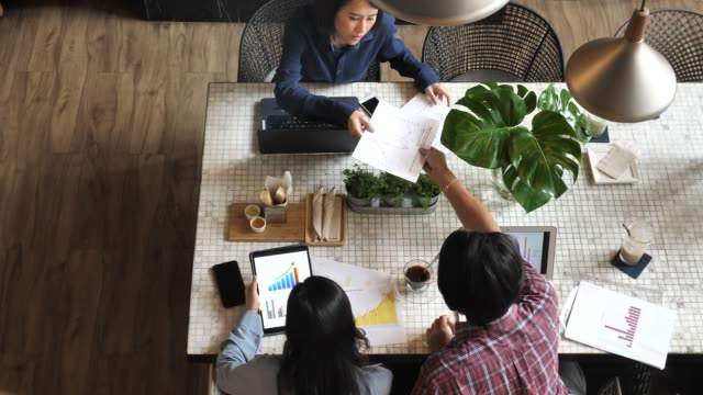 top view of business people meeting at boardroom table discussing financial report using graphs and big data in trendy shared office space - table top view stock videos & royalty-free footage