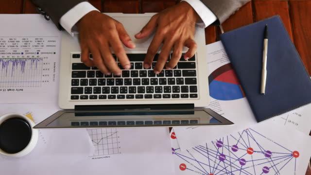 Top vy av affärs man händer att skriva på laptop med en kopp kaffe arbets kammaren Brown