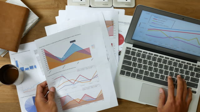 stockvideo's en b-roll-footage met top uitzicht van zakenman werken met laptop en grafiek - rapport