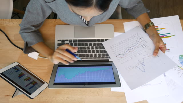 draufsicht der geschäftsfrau, die analyse von finanzdaten mit laptop und digital-tablette, financial - analysieren stock-videos und b-roll-filmmaterial