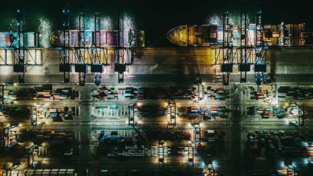 vidéos et rushes de t/l vue supérieure du port industriel occupé avec le navire de récipients la nuit - être ancré