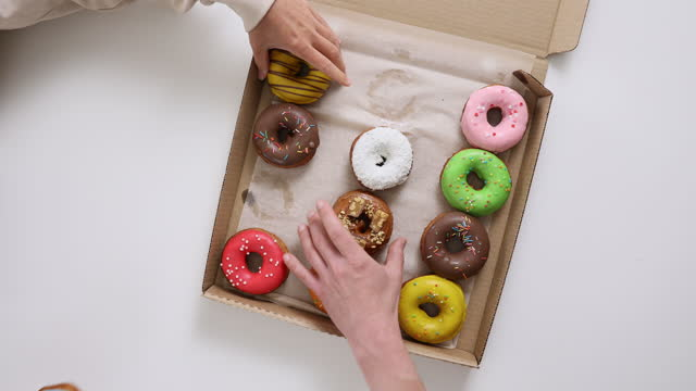 top view of colorful sweet donuts. friends take donuts from the box on the table - moving activity stock videos & royalty-free footage
