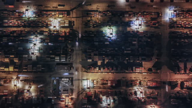 t/l pan top view of container terminal at night - distribution warehouse stock videos & royalty-free footage