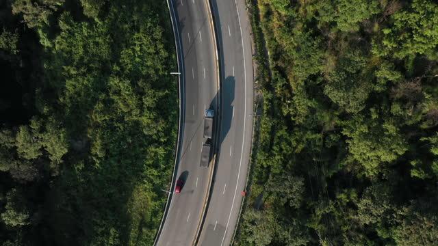 stockvideo's en b-roll-footage met hoogste mening van de vrachtwagenaandrijving van de container op kronkelende weg - kromme