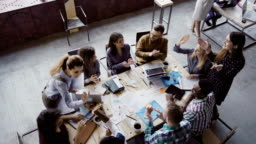 Top view of creative business team working at modern office. Colleagues talking, smiling, high five with each other