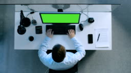 Top View of Diligent Accountant Working at His Desk on a Personal Computer with Green Screen On. Also Signed Papers and Smartphone Laying on His Table.