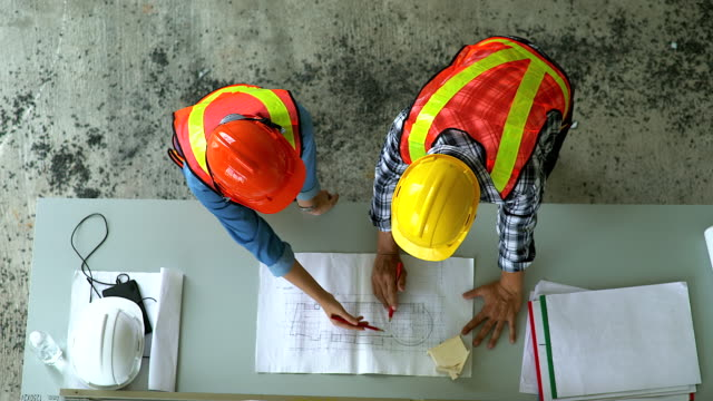 vídeos de stock e filmes b-roll de top view of engineer and site manager looking at paper blueprint plans at a construction site. business concept for the teamwork of heavy industry. - engenheiro