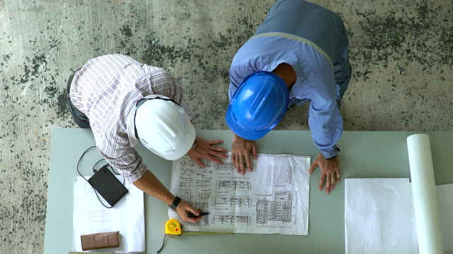 Top view of engineering team of the site manager and field engineer looking at constructed paper blueprint plans at a construction site. Business Concept for the teamwork of heavy industry.