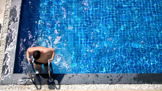 slo mo - top view of fat man getting out from swimming pool - pantaloncino da bagno video stock e b–roll