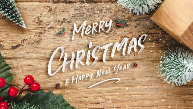 top view of handwriting red merry christmas on rustic wooden table with mini christmas tree and burry leaf with wood home toy with snow fall.winter holiday seasonal greeting card - table top view stock videos & royalty-free footage