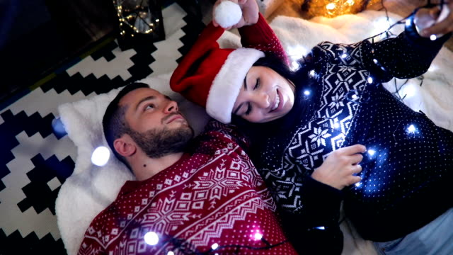 top view of happy couple laying on floor for christmas eve - top garment stock videos & royalty-free footage