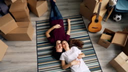 Top view of happy man and woman talking lying on carpet in new flat with boxes