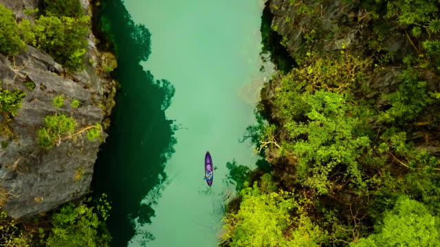 top view of kayak kayaking and enjoying the turquoise water - rock type stock videos and b-roll footage