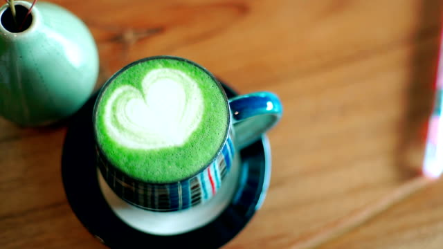 top view of matcha latte with heart shape on a wooden background. - cup stock videos & royalty-free footage
