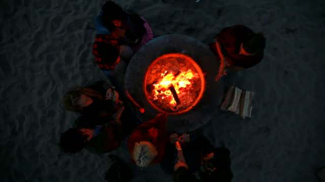 vídeos de stock, filmes e b-roll de ws top view of multi ethnic group around bonfire at beach / venice, california, united states - fogueira fogo ao ar livre