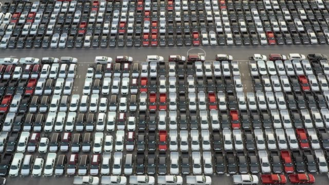 top view of new cars lined up outside an automobile factory for import & export. - car rental stock videos and b-roll footage