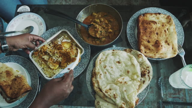 top view of people and variety of indian food served on a dining table - stock video - dining table stock videos & royalty-free footage