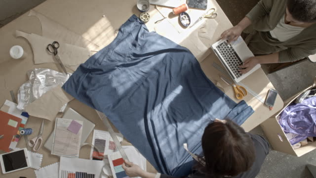 Top view of seamstress using metal ruler to draw straight line on fabric