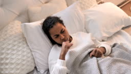 Top View of Sick Young African Girl Coughing while Sleeping in Bed