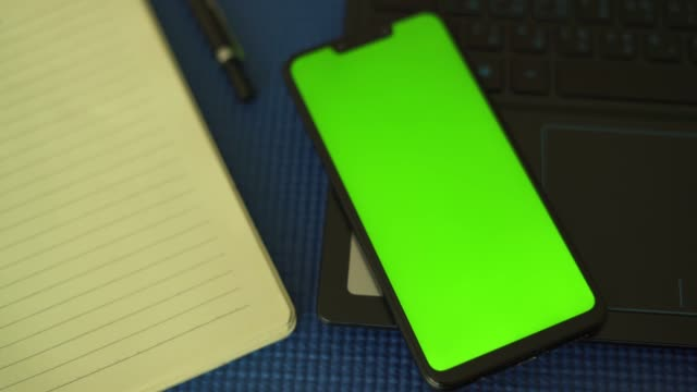 top view of smartphone chroma key green screen smartphone on laptop - table stock videos & royalty-free footage
