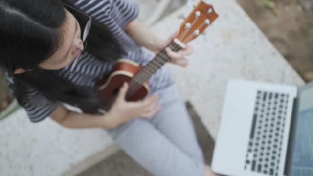 vídeos de stock, filmes e b-roll de visão superior da menina adolescente jogando ukulele com seu amigo ou professor usando laptop de teleconferência em covid-19 ou situação de vírus corona - ukulele