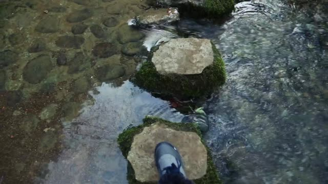 Top view of the foot moving from stone to stone across a stream