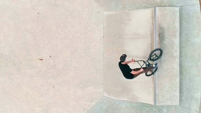 top view of the man riding bike extremally, jumping and doing trick on the bike park - stunt stock videos & royalty-free footage