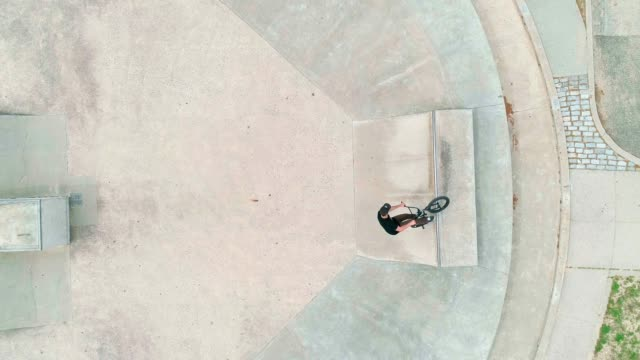 top view of the man riding bike extremally, jumping and doing trick on the bike park - freestyle bmx stock videos and b-roll footage