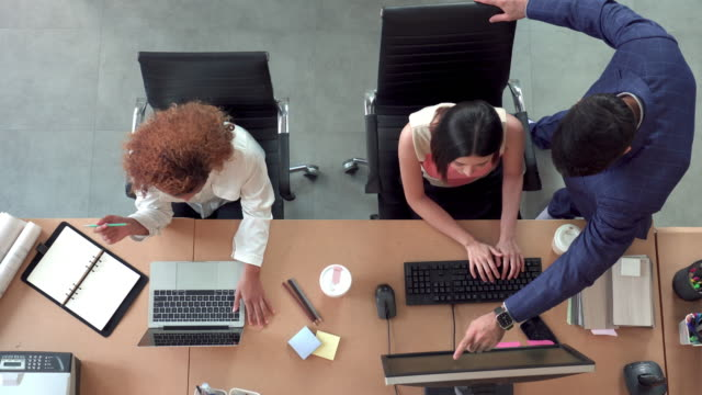 top view of  their boss coming to check asian business woman and colleague 's work on their desk  in the office - desk stock videos & royalty-free footage