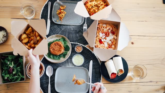 top view of two people's hands sharing takeaway meal at table - fast food stock videos & royalty-free footage