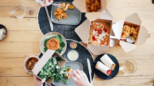 top view of two people's hands sharing takeaway meal at table - convenience stock videos & royalty-free footage