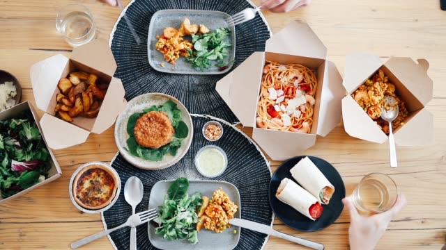 top view of two people's hands toasting with drinks while eating takeaway food - table top view stock videos & royalty-free footage