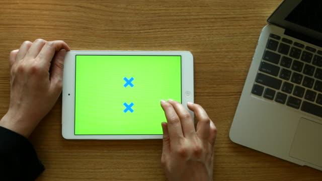 Vista superior de usando tableta digital con ordenador portátil en el escritorio de madera y pantalla verde, 4 K (UHD)