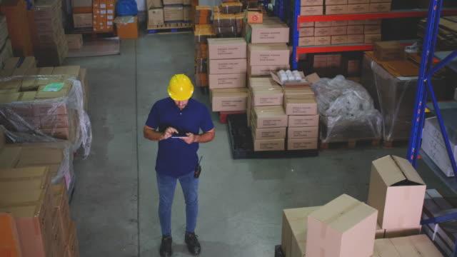 top view of warehouse man worker walk through way between shelf in workplace area - 従業員エンゲージメント点の映像素材/bロール