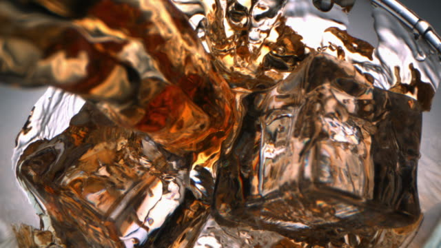 top view of whiskey pouring with a flow inside a glass with ice cubes with camera dollying in - pouring stock videos & royalty-free footage