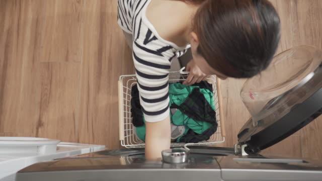 vídeos de stock, filmes e b-roll de vista superior da mulher lavando roupa e carregando roupas na máquina de lavar - lavanderia edifício público