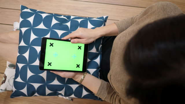 Top view of woman using digital tablet with green screen