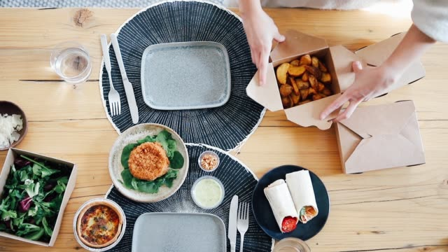 stockvideo's en b-roll-footage met top view of woman's hands opening and arranging takeaway food boxes on the table - table top view