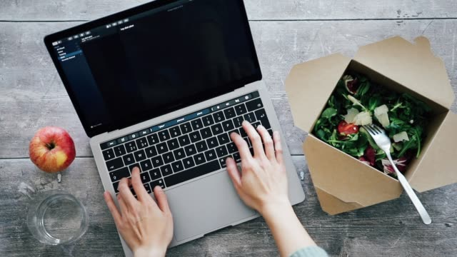 top view of woman's hands typing on laptop while having takeaway lunch - lunch stock videos & royalty-free footage