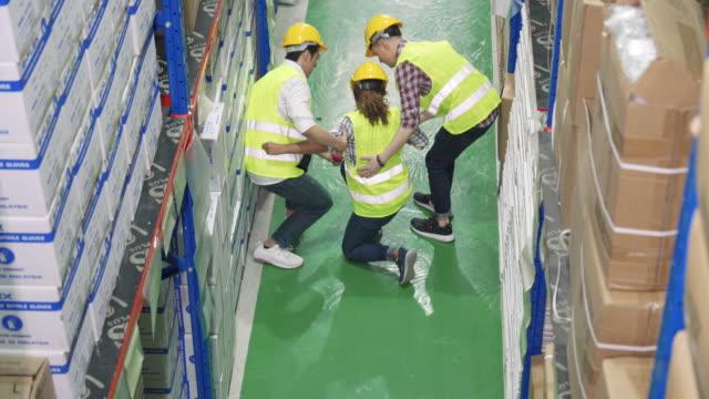 stockvideo's en b-roll-footage met hoogste mening van arbeiders die gekwetst en ongeval op de baan in pakhuis worden - red