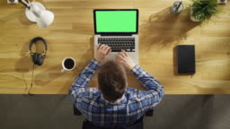 Top View of Young Creative Man Working on His Green Screen Mock-up Laptop Beside Him Lie Headphones, Notebook.